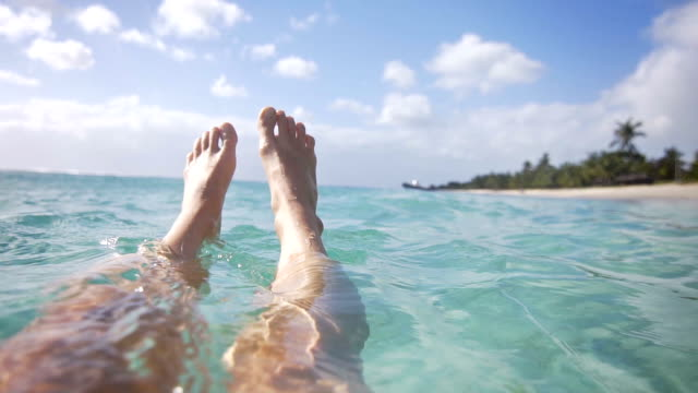 woman relaxing in ocean with her feet floating in water - galleggiare sull'acqua video stock e b–roll
