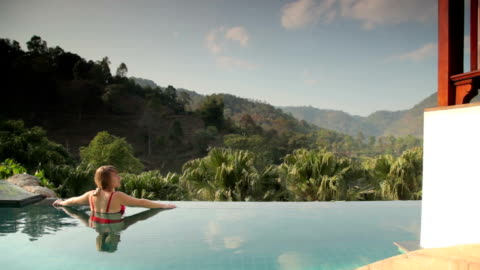 vídeos y material grabado en eventos de stock de mujer relajante en piscina privada de vacaciones - balneario spa