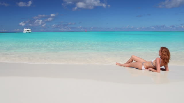 woman relaxing in surf and regarding the horizon - bahamas stock videos & royalty-free footage
