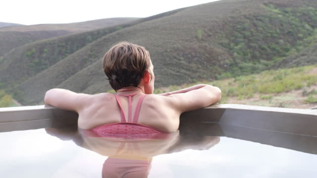 Woman relaxing in the hot outdoor hot tub