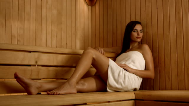hd dolly: woman relaxing in the sauna - sauna stock videos and b-roll footage