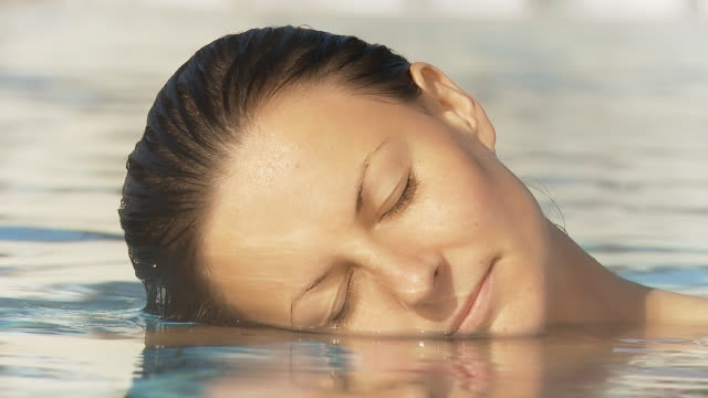 HD: Woman Relaxing In The Swimming Pool