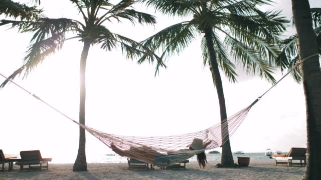 frau entspannen datteln liegend auf hängematte am strand - karibik stock-videos und b-roll-filmmaterial