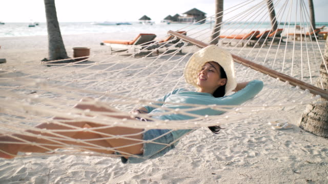 woman relaxing lying down on hammock on beach - sleeping stock videos & royalty-free footage