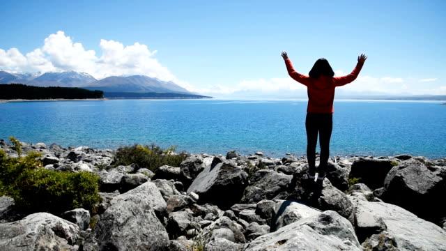 Woman relaxing near the turquoise lake , Pukaki lake Mt.cook , canterbury , New zealand