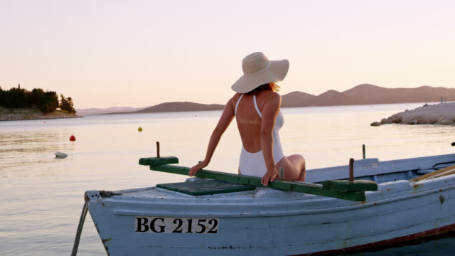 WS Woman relaxing on a boat at sunset