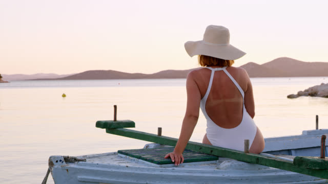 ds woman relaxing on a boat at sunset - hat stock videos and b-roll footage