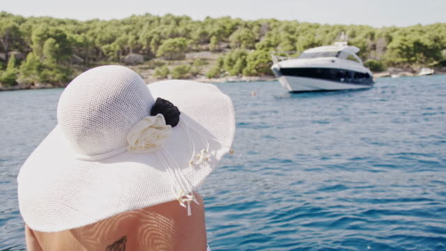 slo mo woman relaxing on a boat - sun hat stock videos & royalty-free footage