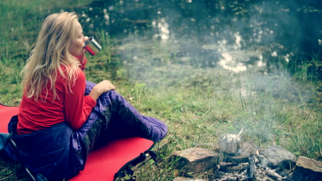 woman relaxing on a lake shore. drinking hot beverage - blouse stock videos and b-roll footage