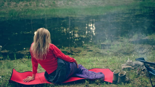 Woman relaxing on a lake shore. Laying in sleeping bag
