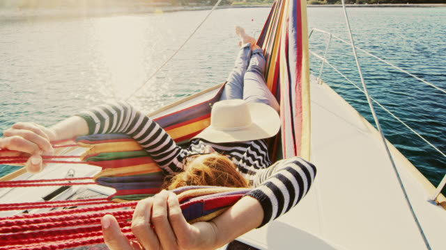 ws woman relaxing on a sailboat - sdraiato video stock e b–roll
