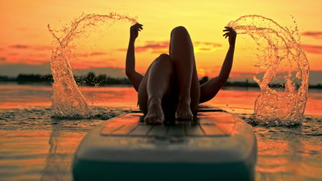super slo mo frau entspannt auf einem surfbrett bei sonnenuntergang - auf dem wasser treiben stock-videos und b-roll-filmmaterial