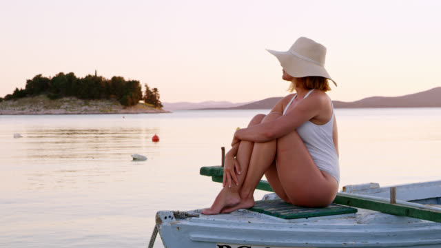 LS Woman relaxing on an old wooden boat at sunset