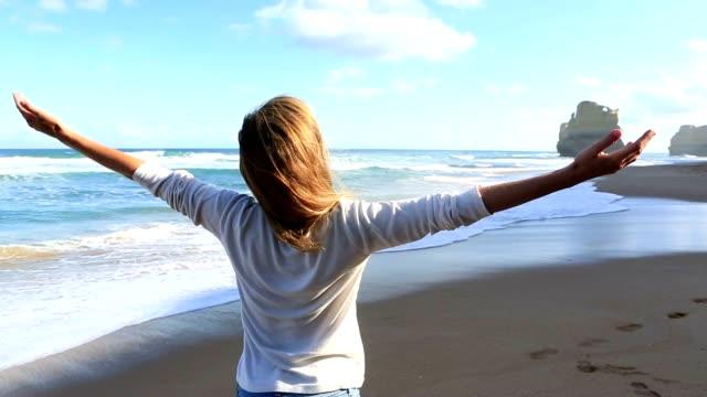 vídeos de stock, filmes e b-roll de mulher relaxante na praia - mãos estendidas