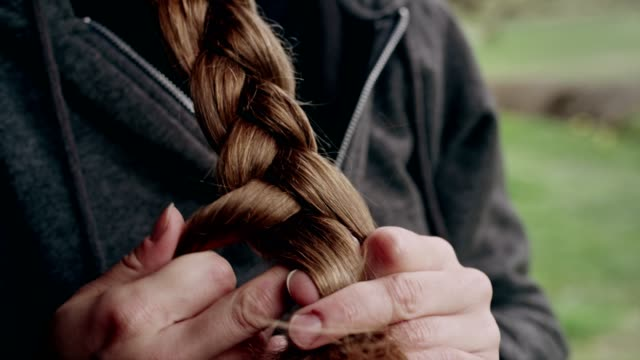 woman relaxing on cabin's porch. braiding her hair - braided hair stock videos & royalty-free footage
