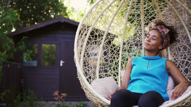 woman relaxing on garden swing seat - wicker stock videos & royalty-free footage