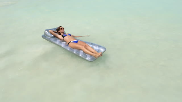 Woman relaxing on inflatable float mattress in ocean