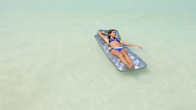woman relaxing on inflatable float mattress in ocean - sonnenbaden stock-videos und b-roll-filmmaterial