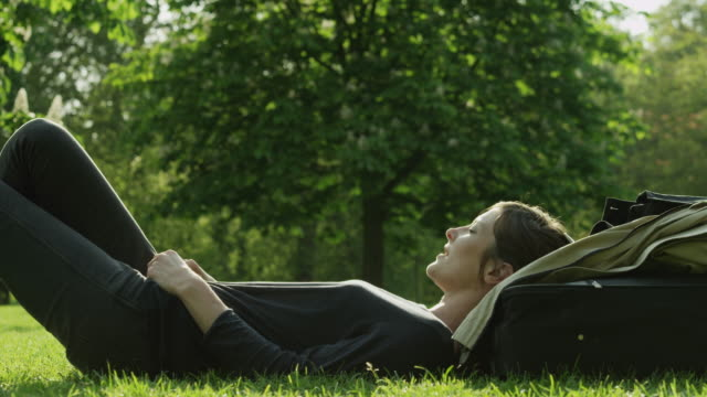 ms woman relaxing on lawn in green park / london, uk - public park stock videos & royalty-free footage