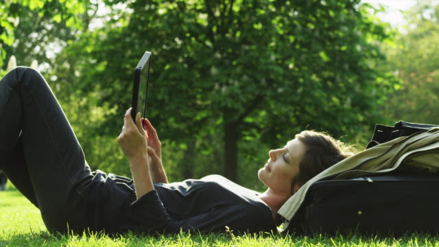 ms woman relaxing on lawn in green park, looking at tablet pc / london, uk - apple computers stock videos & royalty-free footage