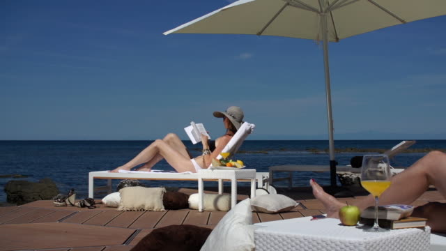 woman relaxing on loung chair at seaside - サングラス点の映像素材/bロール