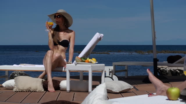 woman relaxing on loung chair at seaside - deck chair stock videos & royalty-free footage
