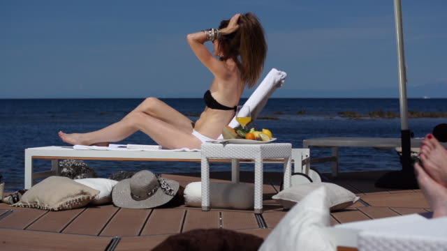 woman relaxing on loung chair at seaside - outdoor chair stock videos & royalty-free footage