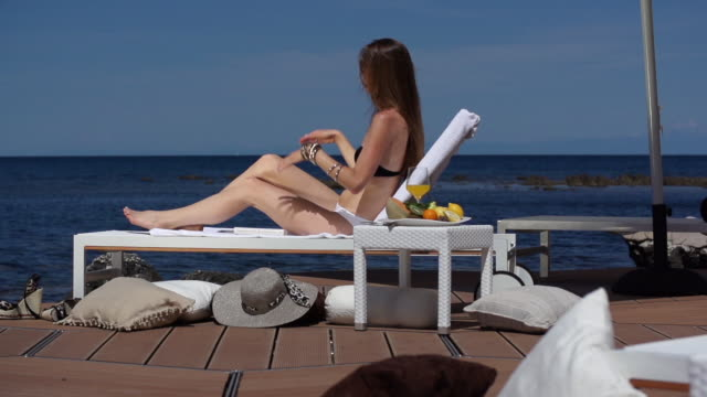 Woman relaxing on loung chair at seaside