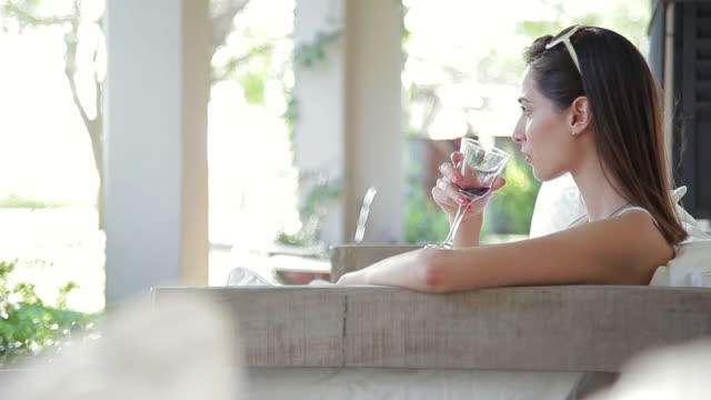 Woman relaxing on porch with glass of wine