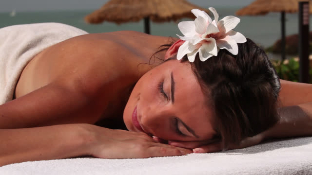 woman relaxing on sunlounger having massage - sdraiato video stock e b–roll