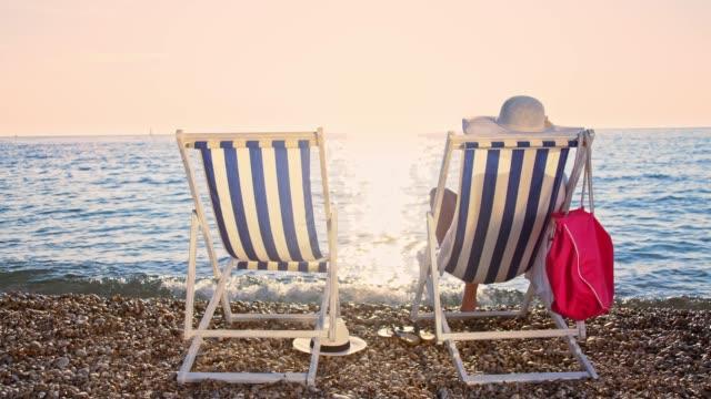 slo mo donna rilassante sulla spiaggia al tramonto - cappello video stock e b–roll