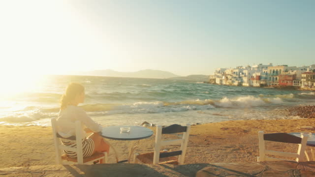 woman relaxing on the beach in mikonos town - greece. - mykonos stock videos and b-roll footage