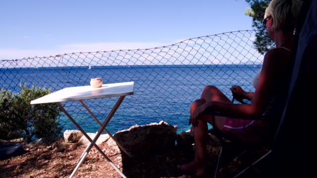 vídeos de stock, filmes e b-roll de ws ds mulher relaxante na praia - cadeira dobrável