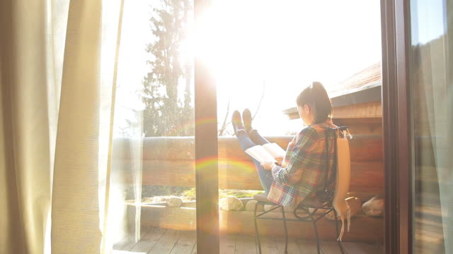 Woman relaxing on the cabin balcony and reading a book.