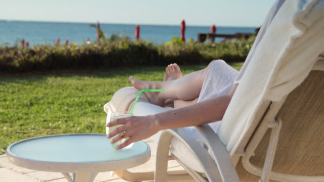 cu woman relaxing outside on sun lounger with a drink. - beach chairs stock videos & royalty-free footage