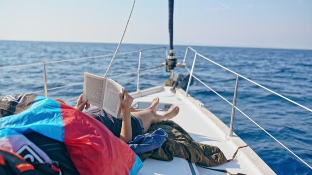 4k woman relaxing, reading book on sunny sailboat, real time - nautical vessel stock videos & royalty-free footage