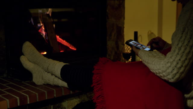 4K Woman relaxing, using smart phone by cozy fireplace, real time