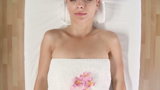 vidéos et rushes de grue haute définition: détente tandis que femme se massage du visage - massage table