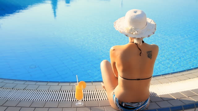 stockvideo's en b-roll-footage met hd dolly: woman relaxing with cocktail by the pool - zwembadrand