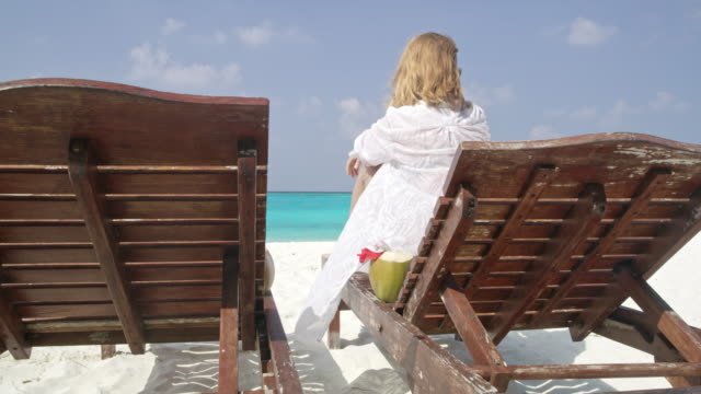 ms woman relaxing with coconut drink on lounge chair on sunny,tranquil tropical ocean beach,maldives - tropical drink stock videos & royalty-free footage
