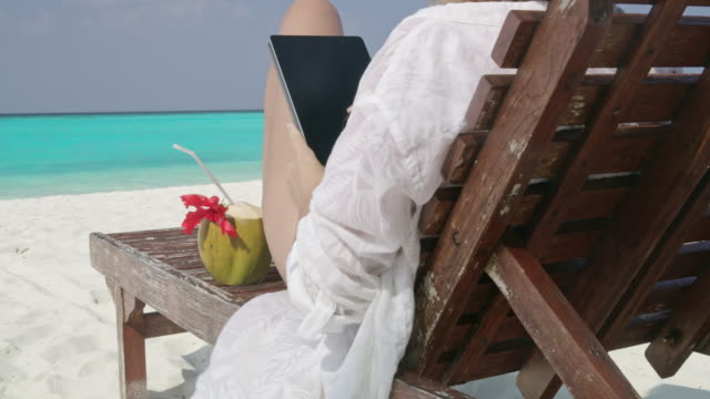 ms woman relaxing with coconut drink,using digital tablet on lounge chair on sunny tropical ocean beach,maldives - tropical drink stock videos & royalty-free footage