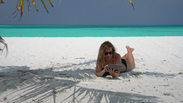 ms woman relaxing with digital tablet on sunny,tropical ocean beach,maldives - turquoise coloured stock videos & royalty-free footage