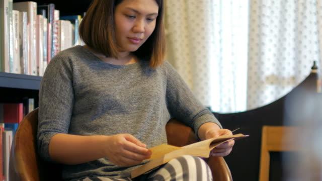 Frau, entspannend mit lesen Sie ein Buch im Wohnzimmer zu Hause, Lifestyle-Konzept