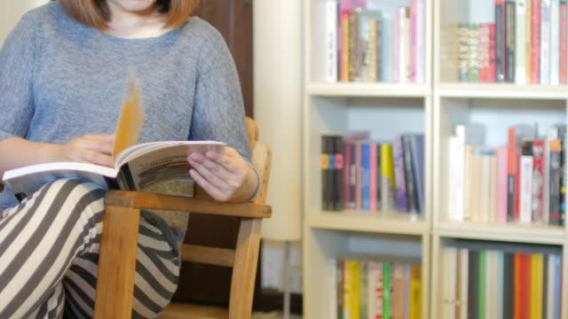 vídeos y material grabado en eventos de stock de mujer relajante con leer un libro en la sala de estar en casa, concepto de estilo de vida - sillón