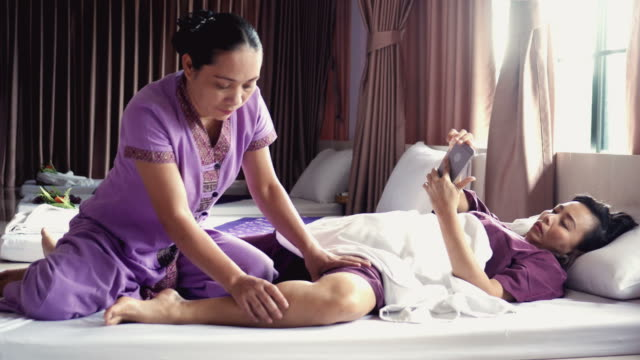 woman relaxing with thai massage and using phone , zoom out - anti aging stock videos and b-roll footage