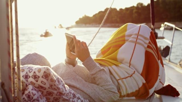 frau, entspannend, eingewickelt in decke mit smartphone auf sonnigen segelboot, real-time - decke bettwäsche stock-videos und b-roll-filmmaterial