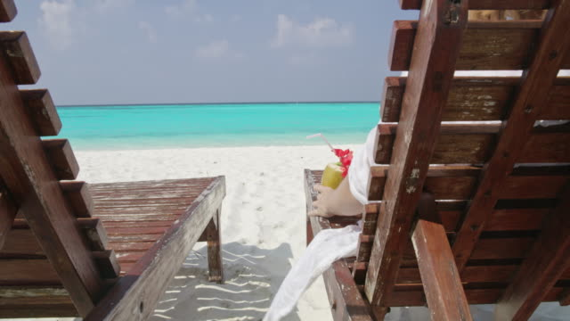 ms woman relaxing,enjoying coconut drink on lounge chair on sunny tropical ocean beach,maldives - tropical drink stock videos & royalty-free footage