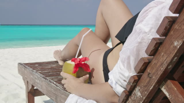 ms woman relaxing,enjoying coconut drink on lounge chair on sunny tropical ocean beach,maldives - tropical drink stock videos and b-roll footage