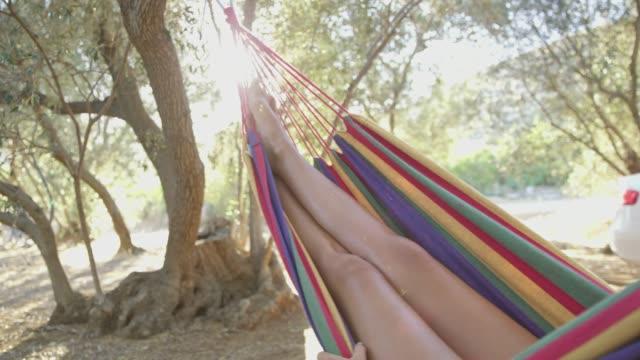 女性がリラックスできる、日当たりの良い夏のキャンプ場でハンモックに揺れる - ハンモック点の映像素材/bロール
