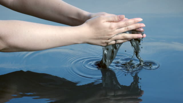 A woman releases a handful of discoloured liquid into clean water reflected in a blue sky.